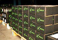 Black Keddco boxes stacked on a wooden pallet in a warehouse